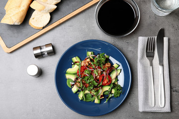 Vegetable salad served with balsamic vinegar on grey table, top view