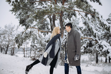 A young beautiful couple is walking in the winter park, hugging and having fun.