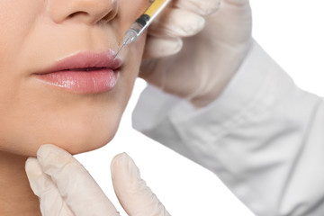 Young woman getting lips injection on white background, closeup. Cosmetic surgery