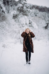 portrait of a young blonde girl in winter forest