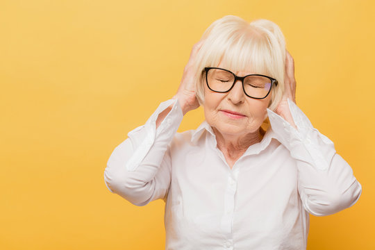 Portrait of senior woman suffering from headache. Health care, pain, stress, age and people concept. Isolated over yellow background.