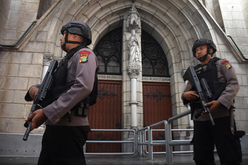 Policemen hold their rifles as they stand guard in front of the Jakarta Cathedral ahead of Christmas celebrations in Jakarta