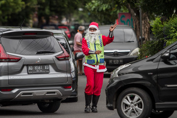 A man dressed as Santa Claus gestures as he arranges traffic in Solo, Central Java