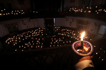 Christians hold candles as they attend a mass on Christmas Eve at Immanuel Church in Jakarta