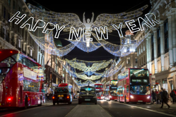 Happy New Year message in shiny silver lettering hanging in front of holiday traffic scene of the streets of London at night