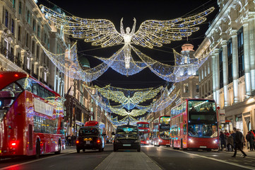 Fond de hotte en verre imprimé Londres bus rouge Red double-decker buses pass under twinkling Christmas lights along the upscale shopping district of Regent Street.