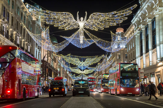 Red double-decker buses pass under twinkling Christmas lights along the upscale shopping district of Regent Street.