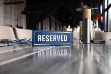 Closeup wooden blue white rectangular plate with the word Reserved standing on gray vintage table in restaurant near to setting, white paper napkins, salt pepper shaker, sugar bowl, vase flowers