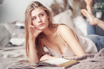 Young woman reading book on bed at home - Image