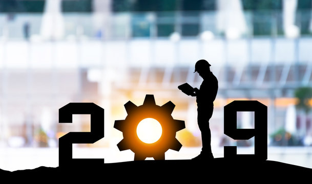 2019 years of robot assistant technology , industry 4.0 , artificial intelligence trend concept. Silhouette of engineer man control automation robo advisor gear in blur smart building bakckground.