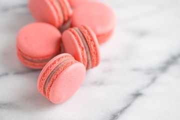 Coral cakes macarons or macaroons on white marble.