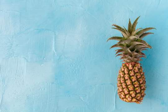 Pineapple with green stem, on blue background. Large space for text. flat layout