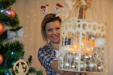 Beautiful women with antlers holding decorative cage full of christmas decoration and smiling