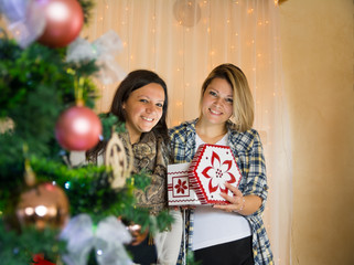 Two beautiful girls open a surprise box on christmas night and watching at the camera