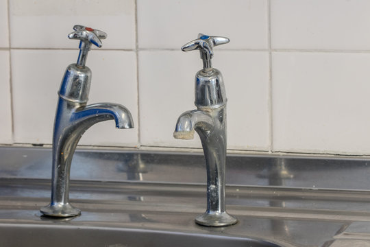 Bad plumbing. Limescale on old chrome tap. Selective focus.