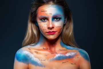 High fashion look of a beautiful stylish woman with bright makeup, written words on her face,