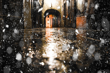 Wall Murals Narrow alley Kilkenny Ireland historic Butterslip alley with snowflakes falling during winter snow storm