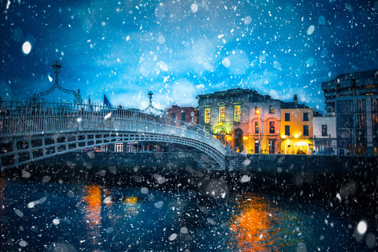 Evening view of Dublin Ireland at the Ha'Penny Bridge of the River Liffey with snowflakes falling during winter snow storm