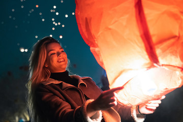 Young smiling European female lighting up a paper sky lantern at event at night