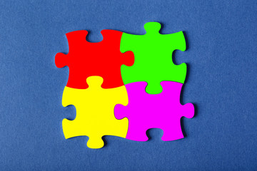 Four fastened puzzles of different colors on blue background