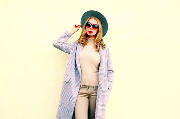Portrait beautiful woman model posing in pink coat, round hat on wall background