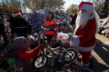 A child receives a bicycle from a firefighter dressed as Santa Claus during the annual gift-giving event organised by the Fire Department, in which they hand out items donated throughout the year to children in need, in Ciudad Juarez
