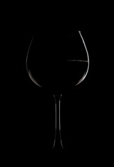 Photo of a glass with wine on a black background. The edges of the glass are illuminated with light.