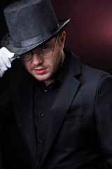 Photo of serious man in black hat in white gloves