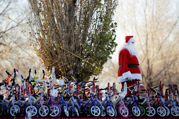 A firefighter dressed as Santa Claus stands by bicycles during the annual gift-giving event organised by the Fire Department, in which they hand out items donated throughout the year to children in need, in Ciudad Juarez