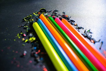 Bright colored pencils and shavings from the pencils on a dark background.