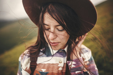 Portrait of happy calm young woman with windy hair. Carefree mood. Amazing atmospheric moment. Stylish hipster girl in hat and backpack walking on top of mountains
