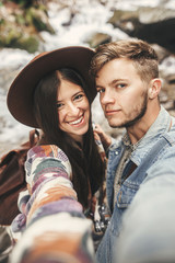 Happy hipster couple making selfie and smiling at waterfall in forest mountains. Stylish couple in love taking selfie photo and having fun. Travel together and Wanderlust concept.