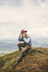 Stylish hipster traveler holding photo camera and taking picture on top of hills on background of foggy mountains. Copy space. Handsome man in hat with backpack traveling in mountains.