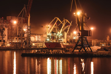 Loading grain in the port. Night panoramic view of the port, cranes and other port infrastructure.