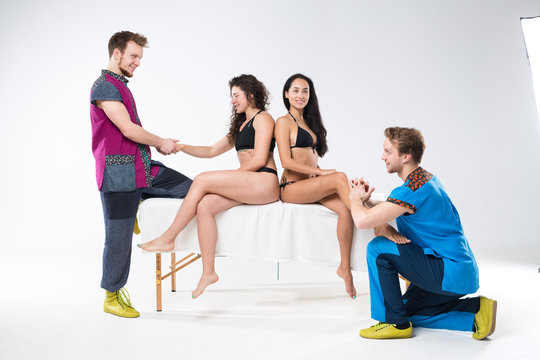 Theme massage and body care. Two twin male brothers doing hand and foot massage of two beautiful sexy women in lingerie sitting on massage table ga isolated white background