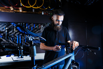 Theme sale and repair of bicycles. Young and stylish with a beard and long hair, a Caucasian man uses a tool to set up and repair a bike in a store. Business owner at work