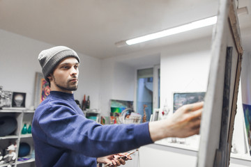 Portrait of a young student artist painting a painting on a canvas in a studio. Student of art school draws a picture. Painting Concept.