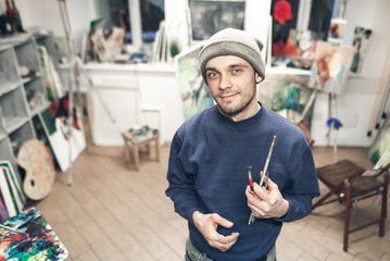 Portrait of a young professional artist, standing in his own studio with brushes in hands, looking camera and smiling.Painter on the background of a studio with paintings, easels, hosts and palettes.