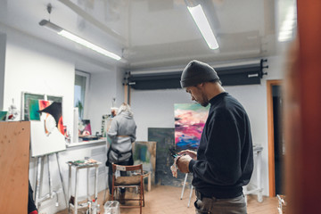 Portrait of a young artist standing in the studio and using the internet on a smartphone,against the background of paintings,easels and the painter paints a picture.Creative atmosphere in art studio