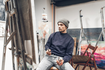 Young professional artist sits on a chair near an easel with a canvas, holds a brush in his hand and, with a cute look, look at the picture. Portrait of the painter in working on the picture.