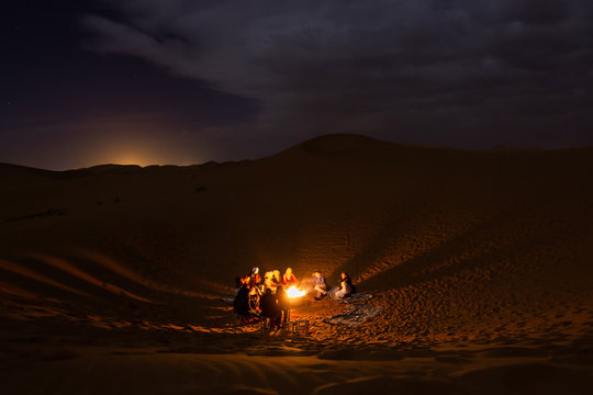 people sitting around a fire in the Sahara desert at night