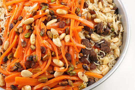 Delicious, colorful Afghan rice pilaf ( Kabuli Pilaf) with lamb or chicken meat and raisin, carrot, pistachio, almond, spices.