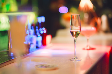 Champagne glass drink-beverage on  a bar.  Selective focus on the foreground glass,night background . Blurred people in the background.  Trendy black stylish  edit. Copy paste space for design concept