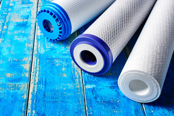 Water filters. Carbon cartridges on a blue background. Household filtration system.