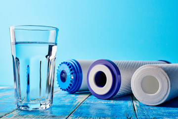 Water filters. Carbon cartridges and a glass on a blue background. Household filtration system.