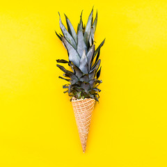 Ice cream cone with pineapple leaves on bright yellow background flat lay top view