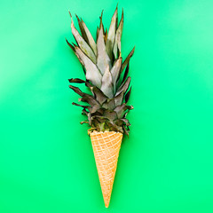 Ice cream cone with pineapple leaves on bright green background flat lay top view
