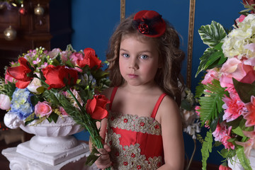 portrait of a little princess girl in a red dress with flowers in her hands
