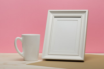 white frame with mug on white desk near pink wall