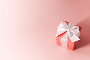 Close view of the box tied with silk ribbon on living coral color pastel background. Gift festive selection.